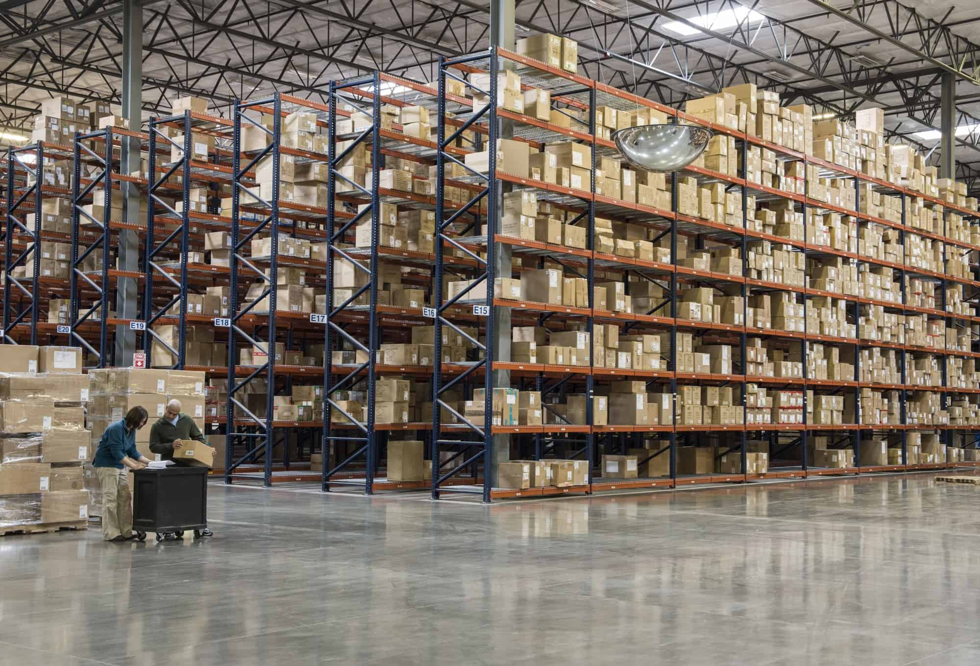 Two employees checking inventory in temporary storage in a distribution warehouse.
